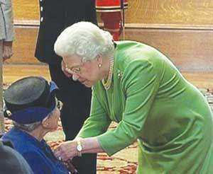 Mrs Self receiving her MBE from HRH the Queen