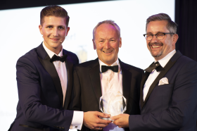 Will Jones receiving his prize from the event compere (left) and Chris Buxton, Chairman of TAF